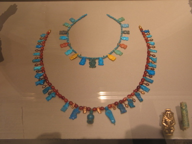 <em>Necklace with Bes and Hathor-Head Pendant</em>, ca. 1390-1352 B.C.E. Faience, Length: 9 15/16 in. (25.2 cm). Brooklyn Museum, Gift of Mrs. Lawrence Coolidge and Mrs. Robert Woods Bliss, and the Charles Edwin Wilbour Fund, 48.66.38. Creative Commons-BY (Photo: , CUR.16.580.201_48.66.38_erg456.jpg)