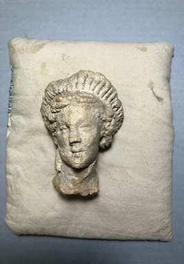 Graeco-Egyptian. <em>Head of a Woman</em>, 30 B.C.E.-100 C.E. Gypsum, 3 7/16 x 2 1/2 in. (8.8 x 6.3 cm). Brooklyn Museum, Gift of Evangeline Wilbour Blashfield, Theodora Wilbour, and Victor Wilbour honoring the wishes of their mother, Charlotte Beebe Wilbour, as a memorial to their father, Charles Edwin Wilbour, 16.580.80. Creative Commons-BY (Photo: , CUR.16.580.80_view01.jpg)
