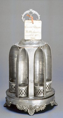 "Edward Gleason. <em>Magic Caster, Patent Model and Label</em>, patented December 1, 1857. White metal, brass, paper, Model: 16 1/4 x 9 x 9 in. (41.3 x 22.9 x 22.9 cm); Label: 3 1/8"" x 2 3/4"". Brooklyn Museum, Purchased with funds given by the Long Island Chapter of the Victorian Society of America, 1992.207a-b. Creative Commons-BY (Photo: Brooklyn Museum, CUR.1992.207a-b.jpg)"