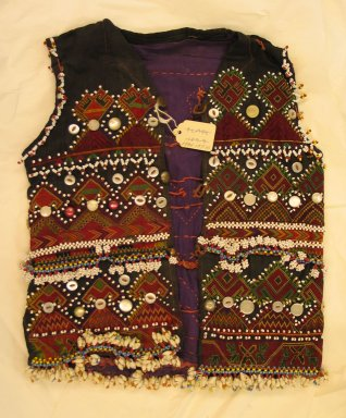 <em>Vest</em>, mid-20th century. Cotton cloth, buttons, coins, metal ornaments, beads, and seashells Brooklyn Museum, Gift of Dr. and Mrs. John P. Lyden, 1994.197.10. Creative Commons-BY (Photo: Brooklyn Museum, CUR.1994.197.10_front.jpg)