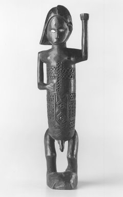 Beembe. <em>Figure of a Standing Male with Left Arm Raised (Mukuya)</em>, 19th or 20th century. Wood, ceramic, 8 1/2 x 2 1/2 x 1 3/4 in. (21.6 x 6.4 x 4.5 cm). Brooklyn Museum, Gift of Drs. Noble and Jean Endicott, 1995.173.3. Creative Commons-BY (Photo: Brooklyn Museum, CUR.1995.173.3_print_front_bw.jpg)