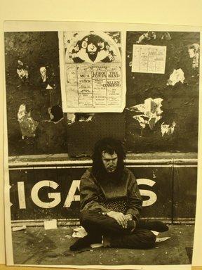 Leon Levinstein (American, 1910-1988). <em>[Untitled] (Man sitting on street beneath 1969 Brooklyn Academy of Music poster, New York)</em>, ca. 1969. Gelatin silver photograph, 13 7/8 x 10 7/8 in. (35.3 x 27.5 cm). Brooklyn Museum, Gift of Stuart Karu, 1995.209.13. © artist or artist's estate (Photo: Brooklyn Museum, CUR.1995.209.13.jpg)