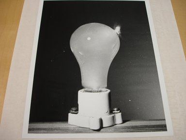Harold Edgerton (American, 1903 - 1990). <em>Bullet in Light Bulb</em>. Gelatin silver photograph, image: 9 1/2 x 7 1/2 in. (24.1 x 19.1 cm). Brooklyn Museum, Gift of The Harold and Esther Edgerton Family Foundation, 1996.166.30. Creative Commons-BY (Photo: Brooklyn Museum, CUR.1996.166.30.jpg)