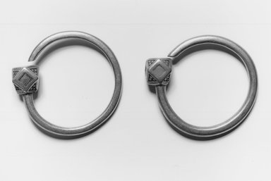 Tuareg. <em>Pair of Earrings (Tsabit)</em>, early 20th century. Silver, 3/4 x 2 1/2 x 2 1/2 in. (1.9 x 6.4 x 6.4 cm). Brooklyn Museum, Gift of Mark S. Rapoport, M.D. and Jane C. Hughes, 1998.12.9a-b. Creative Commons-BY (Photo: Brooklyn Museum, CUR.1998.12.9a-b_print_bw.jpg)