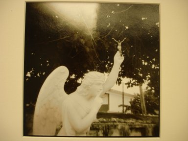Jonathan Bailey (American, born 1954). <em>Isla Mujeres (Quintanar Roo), Mexico, (Angel Holding Christ), Cemetery: Isla Mujeres</em>, 1990. Split-toned gelatin silver photographs, image: 5 1/2 x 5 1/2 in. (14 x 14 cm). Brooklyn Museum, Gift of the artist, 2000.65.1. © artist or artist's estate (Photo: Brooklyn Museum, CUR.2000.65.1.jpg)