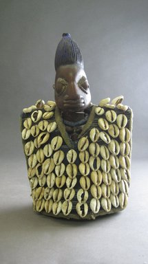 Yorùbá artist. <em>Male twin figure (Ère Ìbejì) with tunic</em>, late 19th or early 20th century. Wood, pigment, cotton cloth, cowrie shells, glass beads, 10 3/4 x 6 3/4 x 4 1/4in. (27.3 x 17.1 x 10.8cm). Brooklyn Museum, Gift of Drs. James J. Strain and Gladys Witt Strain, 2001.122.1a-b. Creative Commons-BY (Photo: Brooklyn Museum, CUR.2001.122.1a-b_overall.jpg)