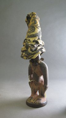 Yorùbá artist. <em>Male twin figure (Ère Ìbejì) with cap</em>, late 19th or early 20th century. Wood, pigment, camwood paste, rayon?, glass and stone beads, 11 1/4 x 2 3/4 x 3in. (28.6 x 7 x 7.6cm). Brooklyn Museum, Gift of Drs. James J. Strain and Gladys Witt Strain, 2001.122.4a-b. Creative Commons-BY (Photo: Brooklyn Museum, CUR.2001.122.4a-b.jpg)