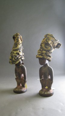 Yorùbá artist. <em>Male twin figure (Ère Ìbejì) with cap</em>, late 19th or early 20th century. Wood, pigment, camwood paste, rayon?, 11 1/2 x 3 x 3 1/4in. (29.2 x 7.6 x 8.3cm). Brooklyn Museum, Gift of Drs. James J. Strain and Gladys Witt Strain, 2001.122.3a-b. Creative Commons-BY (Photo: , CUR.2001.122.4a-b_2001.122.3a-b.jpg)