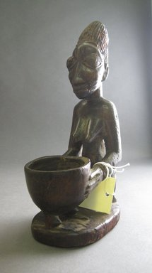 Yorùbá. <em>Kneeling Female Figure Holding Offering Bowl (Olumeye)</em>, late 19th or early 20th century. Wood, 9 x 3 1/4 x 4 1/2in. (22.9 x 8.3 x 11.4cm). Brooklyn Museum, Gift of Drs. James J. Strain and Gladys Witt Strain, 2001.122.5. Creative Commons-BY (Photo: Brooklyn Museum, CUR.2001.122.5_overall.jpg)