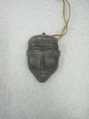 Therese Ukaleannuk. <em>Amulet in the Form of a Head, March 1974</em>, 1950-1980. Gray stone, rawhide, 2 3/4 x 1 3/4 x 3/4 in. (7 x 4.4 x 1.9 cm). Brooklyn Museum, Hilda and Al Schein Collection, 2004.79.27. Creative Commons-BY (Photo: Brooklyn Museum, CUR.2004.79.27.jpg)
