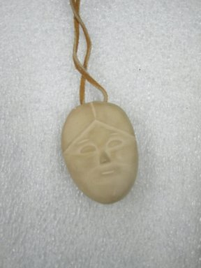 Therese Ukaleannuk. <em>Janus-faced Amulet Head, March 1974</em>, 1950-1980. Tan stone, 2 x 1/2 x 3/4 in. (5.1 x 1.3 x 1.9 cm). Brooklyn Museum, Hilda and Al Schein Collection, 2004.79.28. Creative Commons-BY (Photo: Brooklyn Museum, CUR.2004.79.28.jpg)