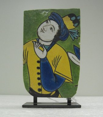 <em>Fragmentary Tile with Figural Decoration</em>, 17th century. Ceramic; fritware, painted in yellow, turquoise, cobalt blue, green, black, opaque white, and ochre brown glazes with manganese purple in the cuerda seca (dry-cord) technique., 6 1/2 x 4 x 2 in. (16.5 x 10.2 x 5.1 cm). Brooklyn Museum, Gift of Mr. and Mrs. Robert L. Poster in memory of Dr. Bertram H. Schaffner, 2010.45.1. Creative Commons-BY (Photo: Brooklyn Museum, CUR.2010.45.1_front.jpg)