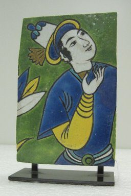 <em>Fragmentary Tile with Figural Decoration</em>, 17th century. Ceramic; fritware, painted in yellow, turquoise, cobalt blue, green, black, opaque white, and ochre brown glazes with manganese purple in the cuerda seca (dry-cord) technique., 6 1/2 x 4 x 2 in. (16.5 x 10.2 x 5.1 cm). Brooklyn Museum, Gift of Mr. and Mrs. Robert L. Poster in memory of Dr. Bertram H. Schaffner, 2010.45.2. Creative Commons-BY (Photo: Brooklyn Museum, CUR.2010.45.2_front.jpg)