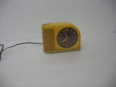 "Westclox, a division of Western Clock Co. (1884-present). <em>""Moonbeam"" Clock</em>, Introduced 1949. Plastic, brass, other metals, rubber electric cord, and plug, 4 7/8 x 6 1/2 x 2 3/8 in. (12.4 x 16.5 x 6.0 cm). Brooklyn Museum, Gift of Arnold Lehman, 2011.15.3. Creative Commons-BY (Photo: Brooklyn Museum, CUR.2011.15.3.jpg)"
