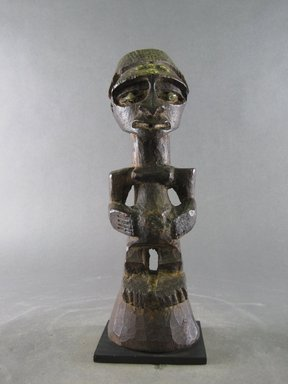 Songye. <em>Figure of Female</em>, 20th century. Wood, copper alloy, organic materials (possibly sacrificial), 14 3/8 x 3 1/8 x 3 9/16 in. (36.5 x 8 x 9 cm). Brooklyn Museum, Gift in memory of Frederic Zeller, 2014.54.48 (Photo: Brooklyn Museum, CUR.2014.54.48_front.jpg)