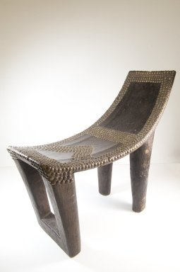 Ngombe. <em>Chief's Seat (Ekele)</em>, late 19th century. Wood, copper alloy, applied material, 20 3/4 x 10 1/2 x 23 1/2 in. (52.7 x 26.7 x 59.7 cm). Brooklyn Museum, Museum Expedition 1922, Robert B. Woodward Memorial Fund, 22.1109. Creative Commons-BY (Photo: Brooklyn Museum, CUR.22.1109_threequarter_PS5.jpg)