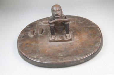 Woyo. <em>Pot Lid with Seated Male Figure (Taampha)</em>, 19th or early 20th century. Wood, stain, 3 1/2 x 8 x 8 in. (8.9 x 20.3 x 20.3 cm). Brooklyn Museum, Museum Expedition 1922, Robert B. Woodward Memorial Fund, 22.1115. Creative Commons-BY (Photo: Brooklyn Museum, CUR.22.1115_front_PS5.jpg)