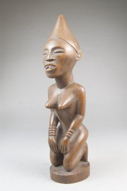 Possibly Vili. <em>Kneeling Female Figure</em>, late 19th or early 20th century. Wood, applied materials, 8 1/2 x 2 3/8 in. (21.6 x 6 cm). Brooklyn Museum, Museum Expedition 1922, Robert B. Woodward Memorial Fund, 22.1140. Creative Commons-BY (Photo: Brooklyn Museum, CUR.22.1140_threequarter_PS5.jpg)