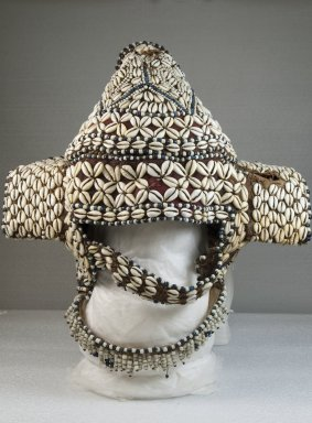 Kuba. <em>Headdress</em>, late 19th or early 20th century. Cowrie shell, fiber, wood, 13 3/4 x 13 3/8 in.  (34.9 x 34.0 cm). Brooklyn Museum, Museum Expedition 1922, Robert B. Woodward Memorial Fund, 22.1443. Creative Commons-BY (Photo: Brooklyn Museum, CUR.22.1443_front_PS5.jpg)