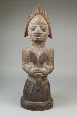 Yorùbá. <em>Figure of a Devotee of Shango Holding an Oshe Shango</em>, late 19th or early 20th century. Wood, pigment, 15 x 4 15/16 x 5 3/4 in. (38.1 x 12.5 x 14.6 cm). Brooklyn Museum, Museum Expedition 1922, Robert B. Woodward Memorial Fund, 22.1518. Creative Commons-BY (Photo: Brooklyn Museum, CUR.22.1518_front_PS5.jpg)