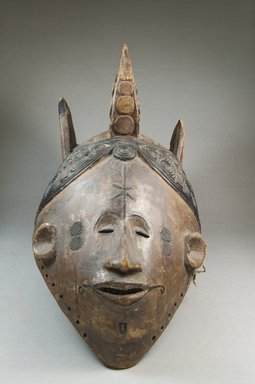 Nupe. <em>Maiden Spirit Mask (Agbogho Mmuo)</em>, 19th century. Wood, cloth, fiber, 16 1/2 x 7 1/4 x 11 in. (41.9 x 18.4 x 27.9 cm). Brooklyn Museum, Museum Expedition 1922, Robert B. Woodward Memorial Fund, 22.1592. Creative Commons-BY (Photo: Brooklyn Museum, CUR.22.1592_front_PS5.jpg)