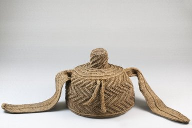 Possibly Kuba (Nkutshu subgroup). <em>Cap With Topknot and Side Extensions</em>, late 19th or early 20th century. Raffia thread, 5 15/16 x 8 7/8 x 8 7/8 in. (15.1 x 22.5 x 22.5 cm). Brooklyn Museum, Museum Expedition 1922, Robert B. Woodward Memorial Fund, 22.1641. Creative Commons-BY (Photo: Brooklyn Museum, CUR.22.1641_front_PS5.jpg)