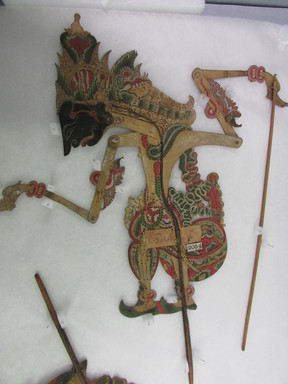 <em>Shadow Play Figure (Wayang kulit)</em>. Leather, pigment, wood, fiber, metal, 16 1/8 × 12 5/8 in. (41 × 32 cm). Brooklyn Museum, Brooklyn Museum Collection, 34.62. Creative Commons-BY (Photo: , CUR.34.62_overall.jpg)