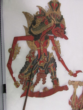 <em>Shadow Play Figure (Wayang kulit)</em>. Leather, pigment, wood, fiber, metal, 21 1/16 × 11 13/16 in. (53.5 × 30 cm). Brooklyn Museum, Brooklyn Museum Collection, 34.64. Creative Commons-BY (Photo: , CUR.34.64_overall.jpg)