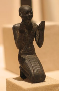 <em>Figure of a Kneeling Priest</em>, ca. 664-332 B.C.E. Bronze, 3 1/8 × 1 1/16 × 1 1/4 in. (7.9 × 2.7 × 3.2 cm). Brooklyn Museum, Charles Edwin Wilbour Fund, 35.1031. Creative Commons-BY (Photo: Brooklyn Museum, CUR.35.1031_wwgA-2.jpg)