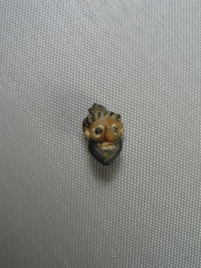 Phoenician. <em>Head Pendant</em>, 4th century B.C.E. Glass, 9/16 x 7/8 in. (1.5 x 2.3 cm). Brooklyn Museum, Gift of Carl Wynn Browne, 37.141. Creative Commons-BY (Photo: Brooklyn Museum, CUR.37.141_view01.jpg)