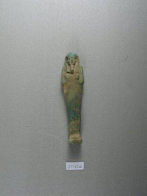 <em>Uninscribed Ushabti</em>, 664-525 B.C.E. Faience, 4 5/16 x 1 x 13/16 in. (11 x 2.5 x 2 cm). Brooklyn Museum, Charles Edwin Wilbour Fund, 37.182E. Creative Commons-BY (Photo: Brooklyn Museum, CUR.37.182E_view1.jpg)