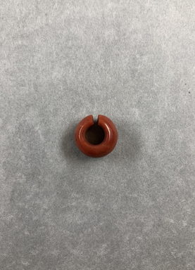 <em>Penannular Earring</em>. Red jasper, Diam. 5/16 × 5/8 in. (0.8 × 1.6 cm). Brooklyn Museum, Charles Edwin Wilbour Fund, 37.1959E. Creative Commons-BY (Photo: , CUR.37.1959E_view01.jpg)