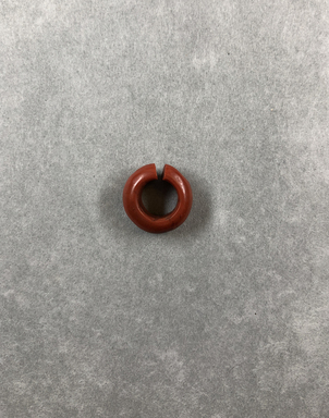 <em>Penannular Earring</em>. Red jasper, Diam. 3/16 × 9/16 in. (0.5 × 1.4 cm). Brooklyn Museum, Charles Edwin Wilbour Fund, 37.1961E. Creative Commons-BY (Photo: , CUR.37.1961E_view01.jpg)