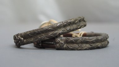 <em>Pair of Bracelets</em>. Stained wood, silver, each: 1/2 x 2 7/8 in. (1.2 x 7.3 cm). Brooklyn Museum, Frank L. Babbott Fund, 37.371.131.1-.2. Creative Commons-BY (Photo: Brooklyn Museum, CUR.37.371.131.1-.2_side.jpg)