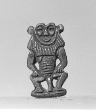 <em>Bes-Image Amulet</em>, 1539-1075 B.C.E. Faience, 1 1/4 × 11/16 × 3/16 in. (3.1 × 1.7 × 0.5 cm). Brooklyn Museum, Charles Edwin Wilbour Fund, 37.915E. Creative Commons-BY (Photo: Brooklyn Museum, CUR.37.915E_negL_897_12A_bw.jpg)