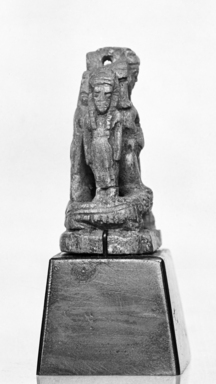 <em>Amulet of Pataikos Flanked by Goddesses</em>. Sericite, 1 3/8 x 7/8 x 11/16 in. (3.5 x 2.3 x 1.7 cm). Brooklyn Museum, Charles Edwin Wilbour Fund, 37.995E. Creative Commons-BY (Photo: , CUR.37.995E_NegID_37.995E_GRPB_cropped_bw.jpg)