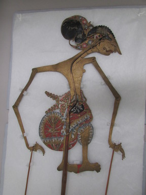 <em>Shadow Play Figure (Wayang kulit)</em>. Leather, pigment, wood, fiber, metal, 26 9/16 × 9 5/8 in. (67.5 × 24.5 cm). Brooklyn Museum, Gift of S. Koperberg, 39.419. Creative Commons-BY (Photo: , CUR.39.419_overall.jpg)