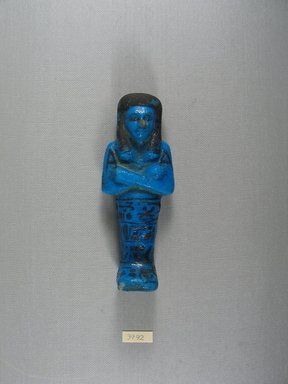 <em>Ushabti of Princess Ist-Em-Kheb</em>, ca. 1075-945 B.C.E. Faience, 5 15/16 x 2 5/16 x 1 7/16 in. (15.1 x 5.8 x 3.7 cm). Brooklyn Museum, Gift of Alvin Devereux, 39.92. Creative Commons-BY (Photo: Brooklyn Museum, CUR.39.92_view1.jpg)
