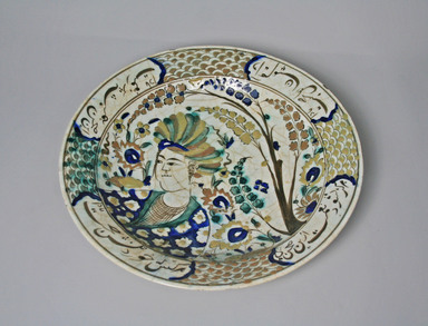 <em>Dish Depicting Turbaned Youth and Persian Poetic Inscriptions</em>, early 17th century. Ceramic, slip, underglaze, glaze, 13 5/8 x 2 9/16 in. (34.6 x 6.5 cm). Brooklyn Museum, Gift of Mrs. Horace O. Havemeyer, 42.212.31. Creative Commons-BY (Photo: Brooklyn Museum, CUR.42.212.31_top.jpg)