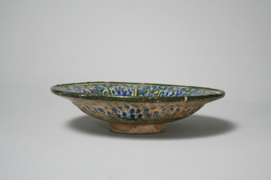 <em>Dish with a Seated Deer</em>, late 13th to 14th century. Ceramic, Sultanabad ware; fritware, painted in black, blue, and turquoise under a transparent glaze, 1 15/16 x 7 9/16 in. (5 x 19.2 cm). Brooklyn Museum, Gift of Mrs. Horace O. Havemeyer, 42.212.9. Creative Commons-BY (Photo: Brooklyn Museum, CUR.42.212.9_exterior.jpg)