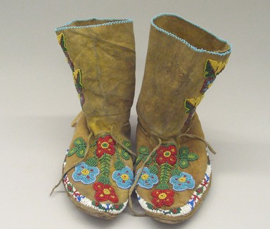 Ute. <em>Pair of Moccasins</em>, early 20th century. Hide, beads, metal buttons, 9 7/16 x 9 7/16 x 3 3/8 in. (24 x 24 x 8.6 cm). Brooklyn Museum, Anonymous gift in memory of Dr. Harlow Brooks, 43.201.67a-b. Creative Commons-BY (Photo: Brooklyn Museum, CUR.43.201.67a-b_view1.jpg)