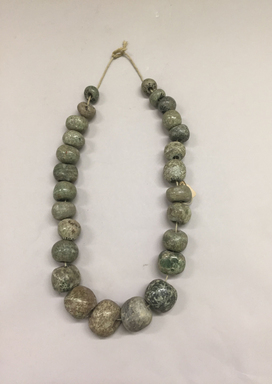 <em>Circular Stone Beads (26) now Strung on Cotton Like a Necklace</em>. Greenstone, plastic monofilament (modern), 5 × 1 × 12 in. (12.7 × 2.5 × 30.5 cm). Brooklyn Museum, Anonymous gift in memory of Dr. Harlow Brooks, 43.201.78. Creative Commons-BY (Photo: , CUR.43.201.78-1.jpg)