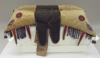 Red River Metis. <em>Pad Saddle</em>, early 19th century. Hide, beads, Stroud cloth, quills, cotton fringe, silk ribbon, deer hair, glass beads, brass, 26 x 18 1/2 in. (66 x 47 cm). Brooklyn Museum, Henry L. Batterman Fund and the Frank Sherman Benson Fund, 50.67.14. Creative Commons-BY (Photo: Brooklyn Museum, CUR.50.67.14_view1.jpg)