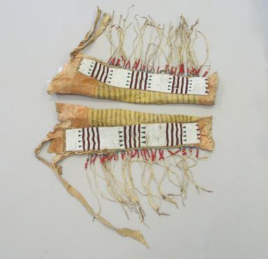 Blackfoot, Piegan. <em>Pair of Chief's Fringed Dress Leggings</em>, early 19th century. Hide, beads, red cloth binding,ermine fur, pigment wood Brooklyn Museum, Henry L. Batterman Fund and Frank Sherman Benson Fund, 50.67.5b-c. Creative Commons-BY (Photo: Brooklyn Museum, CUR.50.67.5b-c_view1.jpg)