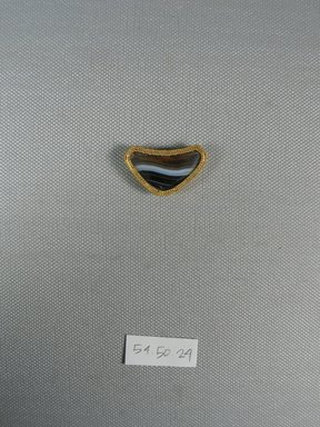 <em>One of Eleven Triangular Stones</em>, ca. 410 B.C.E. Gold, agate, 11/16 x 3/16 x 1 1/4 in. (1.8 x 0.5 x 3.2 cm). Brooklyn Museum, Charles Edwin Wilbour Fund, 54.50.24. Creative Commons-BY (Photo: Brooklyn Museum, CUR.54.50.24_view1.jpg)