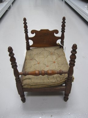 American. <em>Miniature Four Poster Bed</em>, early 19th-mid 19th century. Wood (cherry?); cotton, wool, other textile, 20 x 14 1/2 x 19 in. (50.8 x 36.8 x 48.3 cm). Brooklyn Museum, Gift of Mrs. Charles E. Rogers, Jr., 57.181.2a-b. Creative Commons-BY (Photo: Brooklyn Museum, CUR.57.181.2_view3.jpg)