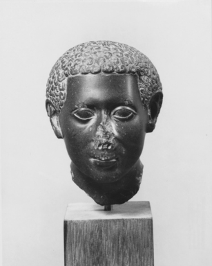 <em>Curly-Haired Youth</em>, 150-30 B.C.E. Green siltstone or greywacke, 4 7/16 x 3 1/4 x 3 3/4 in. (11.2 x 8.3 x 9.5 cm). Brooklyn Museum, Charles Edwin Wilbour Fund, 62.2. Creative Commons-BY (Photo: , CUR.62.2_NegA_print_bw.jpg)