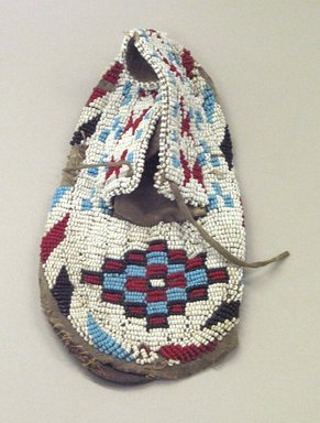 Sioux. <em>Moccasin with red, white, blue and black geometric beadwork</em>, 1901-1966. Beads, cotton thread, hide, 7 3/4 x 3 1/2 x 3/4 in. or (19.0 cm). Brooklyn Museum, Gift of Mr. and Mrs. Jerome Blum, 66.86.24. Creative Commons-BY (Photo: Brooklyn Museum, CUR.66.86.24_view1.jpg)