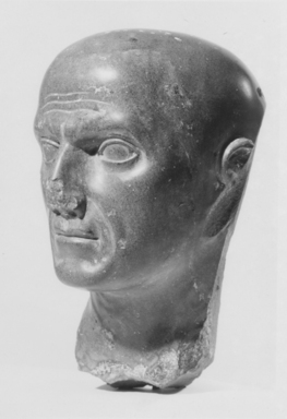 <em>Male Head</em>, 1st-2nd century C.E. Metamorphic schist, 7 3/8 x 4 9/16 x 5 3/16 in. (18.8 x 11.6 x 13.1 cm). Brooklyn Museum, Charles Edwin Wilbour Fund, 69.1. Creative Commons-BY (Photo: Brooklyn Museum, CUR.69.1_NegB_print_bw.jpg)