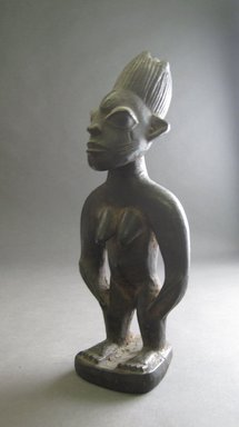 Yorùbá artist. <em>Female twin figure (Ère Ìbejì)</em>, late 19th or early 20th century. Wood, 9 3/4 x 4 x 3 3/8 in.  (24.8 x 10.2 x 8.6 cm). Brooklyn Museum, Gift of Jerome Furman, 70.106.1. Creative Commons-BY (Photo: Brooklyn Museum, CUR.70.106.1_overall.jpg)